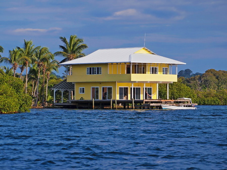Tropical stilt house over the water with a boat at dock, Caribbean sea, Bocas del Toro, Panama