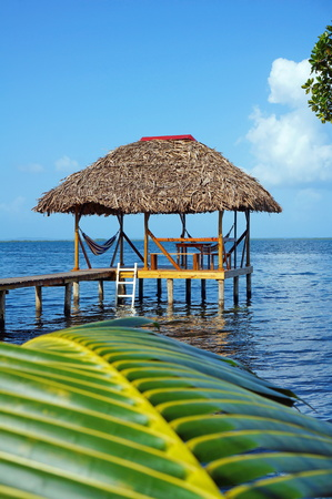 Tropical hut over water with thatched roof and a palm leaf in foreground Stock Photo