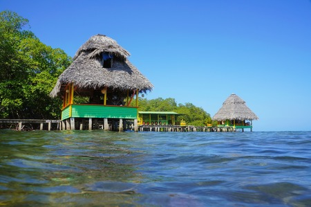 Tropical huts with thatched roof over the sea, Caribbean, Bocas del Toro, Panama Stock Photo