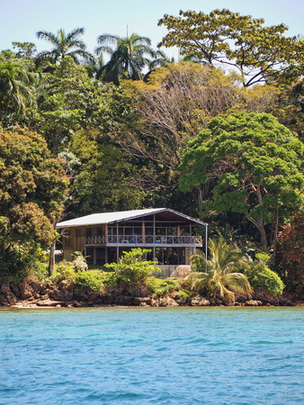 Waterfront Caribbean home surrounded by lush tropical vegetation, Bocas del Toro, Panama