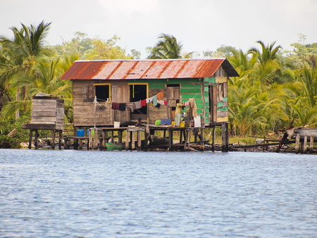 Rustic Amerindian house on stilts over the water with coconut trees in background, archipelago of Bocas del Toro, Panama, Caribbean sea