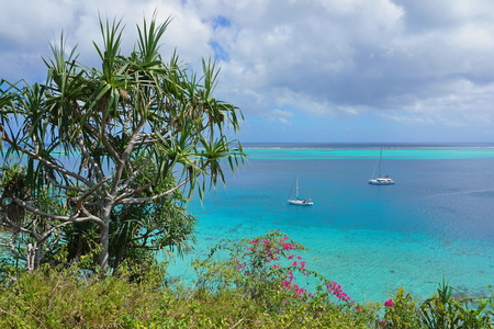 Green vegetation and sailboat anchored in blue water of a tropical lagoon, south Pacific ocean, Huahine island, French Polynesia Stock Photo