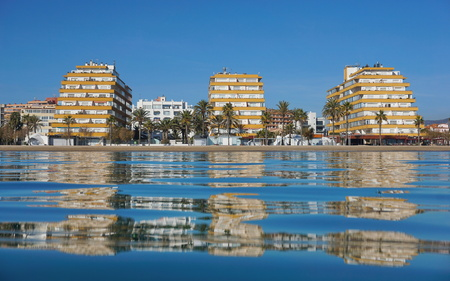 Spain Costa Brava seaside town with apartment buildings on the waterfront seen from water surface, Mediterranean sea, Santa Margarida, Roses, Catalonia, Girona Banco de Imagens