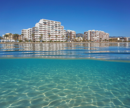 Spain Costa Brava coastline with apartment buildings and sand underwater, split view above and below water surface, Mediterranean sea, Roses, Catalonia, Girona