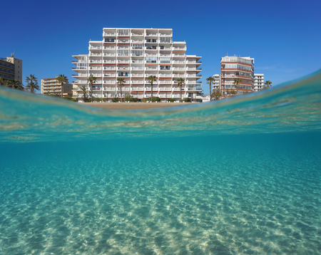 Beachfront apartment building and sandy seabed underwater, split view above and below water surface, Mediterranean sea, Spain, Costa Brava, Roses, Catalonia, Girona Banco de Imagens