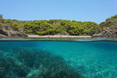 Mediterranean sea peaceful cove with seagrass underwater, split view above and below water surface, Spain, Costa Brava, Cala Guillola, Cadaques, Cap de Creus, Catalonia