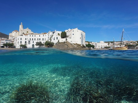 Spain Cadaques village on the shore of the Mediterranean sea with seagrass and a shoal of small fish underwater, split view above and below water surface, Costa Brava
