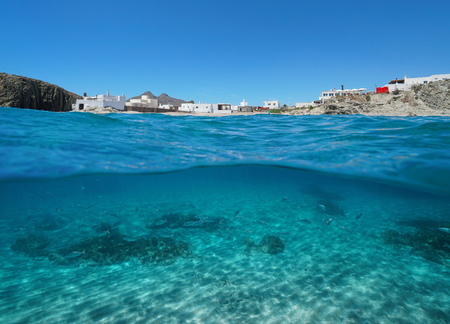 The picturesque village La Isleta del Moro on the seashore with fish and sand underwater, split view above and below water surface, Mediterranean sea, Cabo de Gata-Níjar, Almeria, Andalusia, Spain