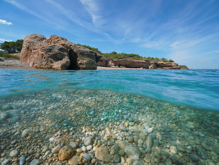 Pebble beach with rocky coast, split view half above and underwater surface, Cala Xelin, Mediterranean sea, Catalonia, LAmetlla de Mar, Tarragona, Costa Dorada, Spain Reklamní fotografie