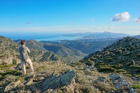 Spain landscape a man standing looking at view from the Albera mountain range with the Mediterranean sea and the Cap de Creus in background, Pyrenees, Catalonia, Alt Emporda Banque d'images - 117727636