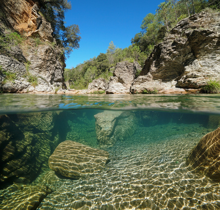 Wild river with rocks over and underwater, split view half above and below water surface, La Muga, Catalonia, Spain Banque d'images - 117727642
