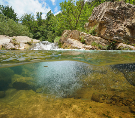 Wild rocky river, split view half over and underwater surface, La Muga, Catalonia, Spain Banque d'images - 117727644
