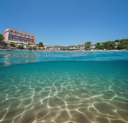 Spain beach with an hotel in Llanca on the Costa Brava and a sandy seabed underwater, split view half over and under water, Mediterranean sea, Platja de Grifeu, Catalonia