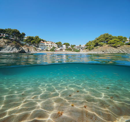 Spain beach in Llanca on the Costa Brava with a sandy seabed and small fish underwater, split view half over and under water, Mediterranean sea, Platja de les Tonyines, Catalonia Banque d'images - 117727651