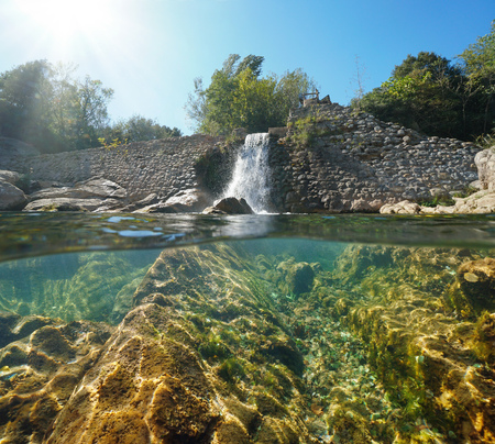 Old stone dam on the river with rocks underwater, split view half above and below water surface, Sant Llorenc de la Muga, Catalonia, Spain Banque d'images - 117727652