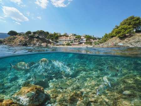 Spain coastline with sea breams fish underwater, les Tonyines beach in Llanca on the Costa Brava, split view half over and under water, Mediterranean sea, Catalonia