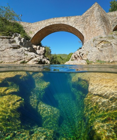 River with an old stone bridge and eroded rocks underwater, split view half above and below water surface, Sant Llorenc de la Muga, Catalonia, Spain Banque d'images - 117727725