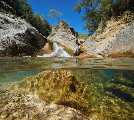 Wild rocky river, split view half over and underwater surface, La Muga, Catalonia, Spain Banque d'images - 117727728