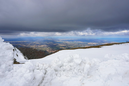 France view over the Roussillon plain with snow in foreground and cloudy sky, massif des Alberes, Pyrenees Orientales Banque d'images - 117727821