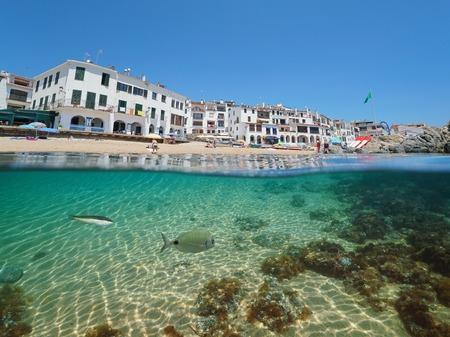 Spain Calella de Palafrugell Mediterranean village, beach shore with fish underwater sea, Costa Brava, Catalonia, split view half over and under water Banque d'images - 117727824