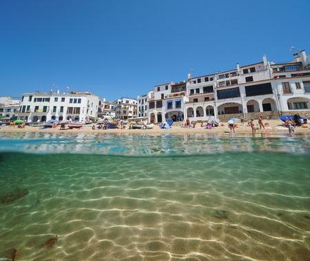 Spain Calella de Palafrugell village, beach shore in summer with sand underwater, Costa Brava, Mediterranean sea, Catalonia, split view half over and under water Banque d'images - 117728021