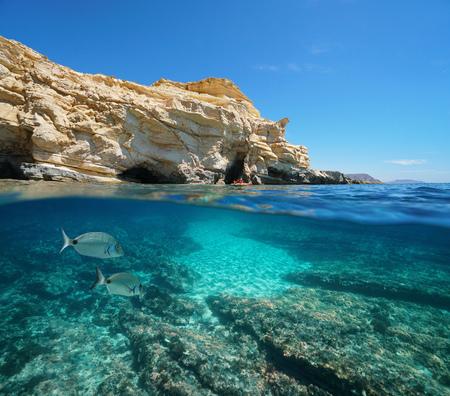 Spain rocky coast with fish underwater in the Cabo de Gata Nijar natural park near Las Negras, Mediterranean sea, Almeria, Andalusia, split view half over and under water Banque d'images - 117728071