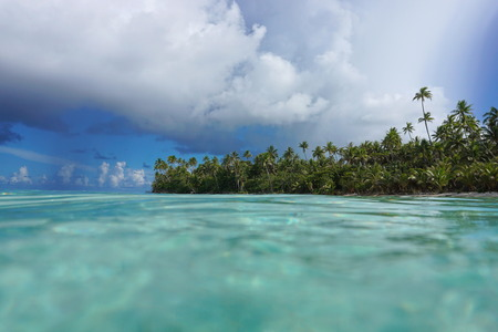 Tropical island coast with lush vegetation seen from water surface, French Polynesia, Huahine, Pacific ocean