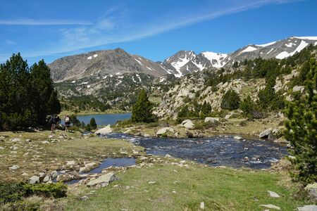 France Pyrenees-Orientales mountain landscape, stream and Comassa lake with Carlit massif in background, natural park of the Catalan Pyrenees