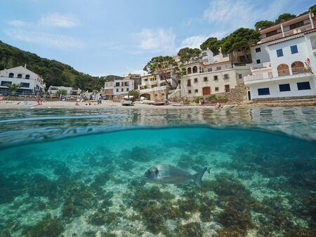 Spain coastal Mediterranean village and sea bream fish underwater, Costa Brava, Sa Tuna, Begur, Catalonia, split view half over and under water