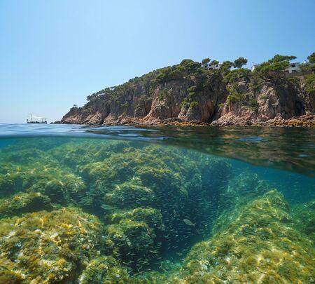 Spain rocky coast with a shoal of small fish underwater, Mediterranean sea, split view half above and below water surface, Costa Brava, Aigua Xelida, Palafrugell, Catalonia Reklamní fotografie