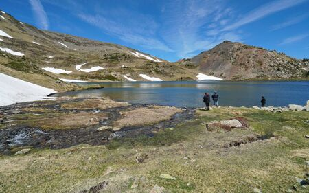 Mountain lake with fishermen, landscape in the natural park of the Catalan Pyrenees, France, Pyrenees-Orientales