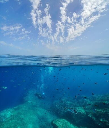 Seascape of Mediterranean sea, many fish with scuba divers underwater and blue sky with cloud, split view over and under water surface, France, Occitanie, Pyrenees-Orientales Reklamní fotografie