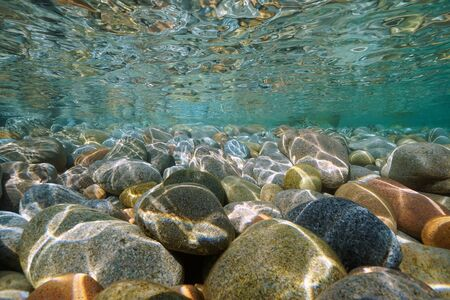 Pebbles stone underwater below water surface near sea shore, natural scene, Mediterranean, Cote d'Azur, France