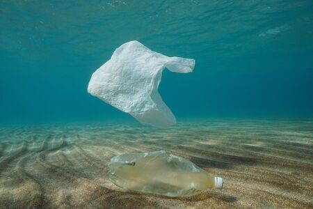 Plastic ocean pollution underwater, a plastic bag adrift and a bottle on a sandy bottom