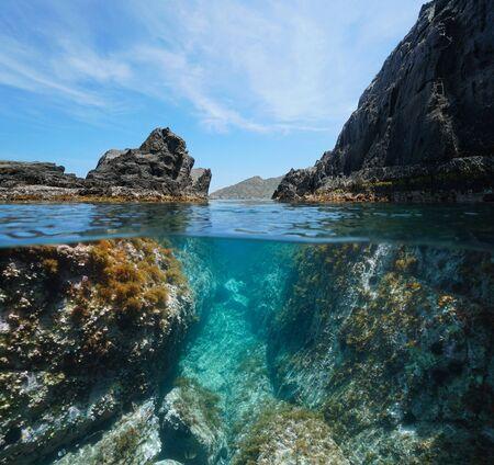 Rocky coast with a passage between rocks, split view over and under water surface, Mediterranean sea, Spain, Costa Brava, El Port de la Selva, Catalonia