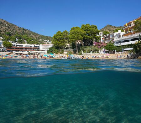Mediterranean sea urban beach in summer in Spain on the Costa Brava with sand underwater, split view over and under water surface, Catalonia, Roses, Canyelles Petites