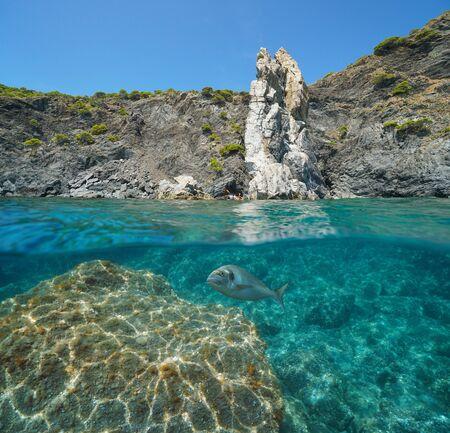 Rocky coast seascape in the Mediterranean sea, split view over and under water surface, Spain, Costa Brava, Colera, Catalonia, La Veta Blanca Stock Photo