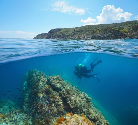 Mediterranean sea scuba diving, two divers underwater and rocky coastline in the Marine reserve of Cerbere Banyuls, split view over and under water surface, France, Occitanie, Pyrenees-Orientales