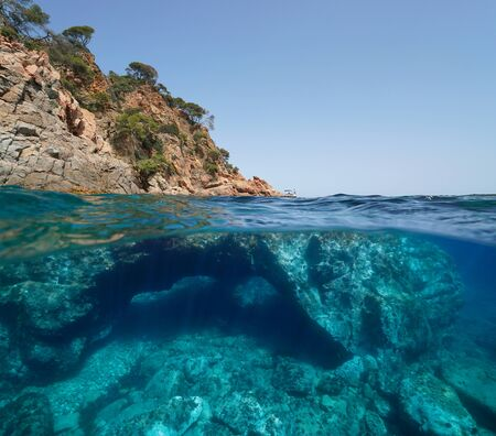 Rocky coast and large rock with a hole underwater, split view over and under water, Mediterranean sea, Spain, Costa Brava, Catalonia, Calella de Palafrugell