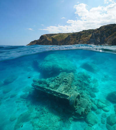 France Occitanie, rocky coast and the remains of a wrecked ship underwater, split view over and under water surface, Mediterranean sea, Marine reserve of Cerbere Banyuls