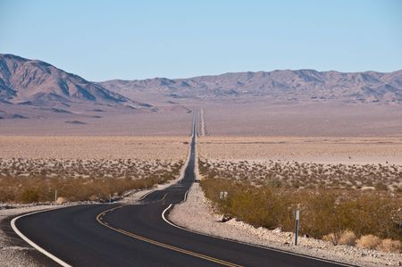Scenic bending and wavy road in the desert surrounded by mountains photo