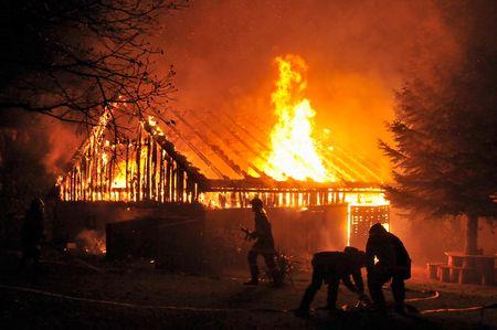 quemado: Casa en fuego en la noche. Bomberos luchando con fuego.