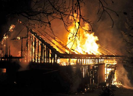 house on fire: Casa en fuego en la noche. Bomberos luchando con fuego.