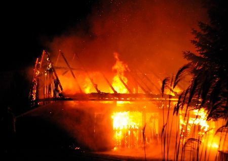 natural disasters: House in fire at night. Firefighters fighting with fire.