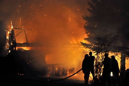 bombero de rojo: Casa en fuego en la noche. Bomberos luchando con fuego.