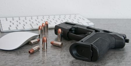 SIG PRO pistole with bullets on the table near mouse and keyboard