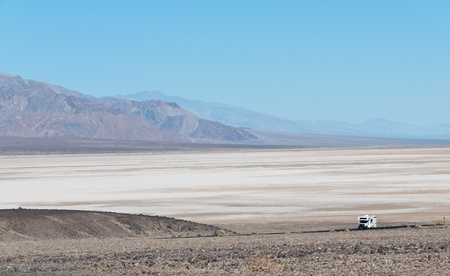 Dried salt fieldwith lonaly caravan on the road of Death Valley