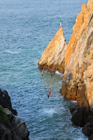 Group of cliff divers enters the water photo
