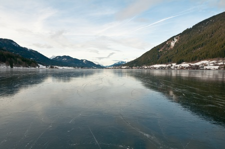 Mountain lake in Austrian Alps covered by mirror ice