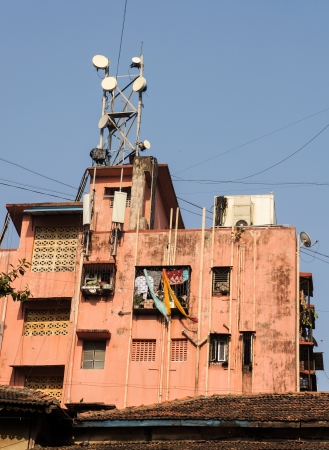 Apartment house in Mumbai with typical balconies, modern telecom antennes, air condition unit and externbal water communications